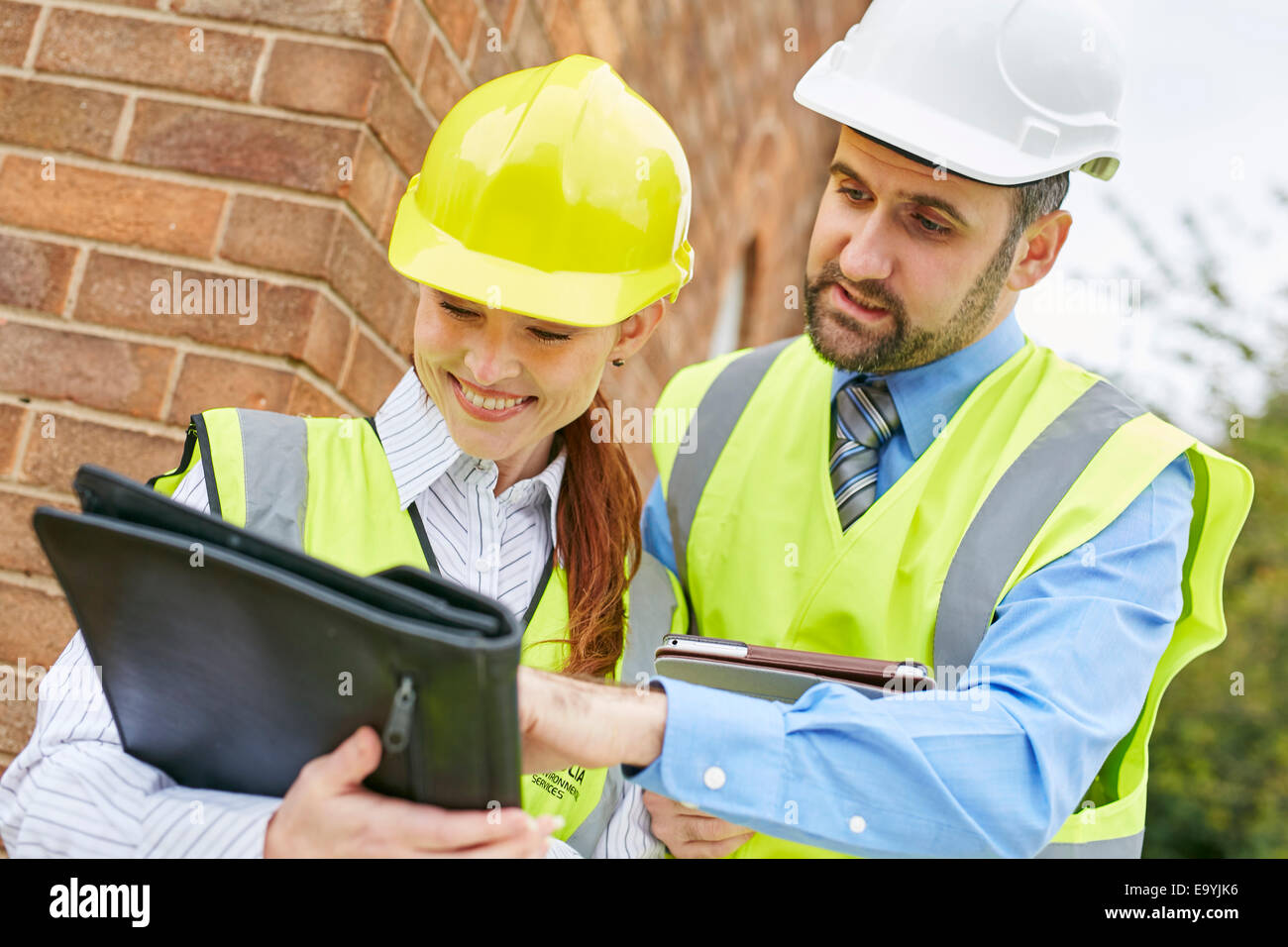 Architects discussing plans at a building site - Stock Image