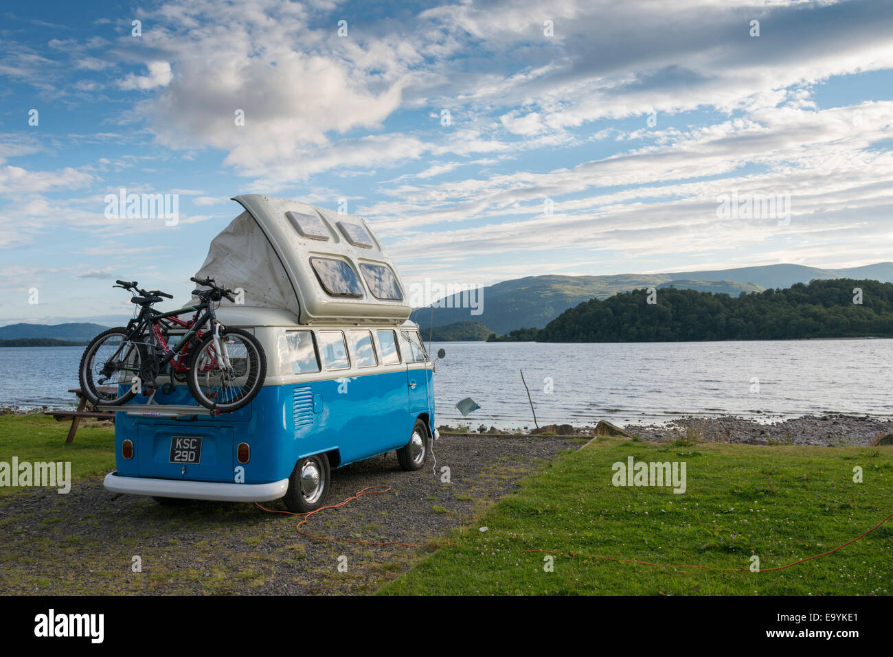 A blue VW campervan parked on the shore of Loch Lomond Scotland UK in summer - Stock Image