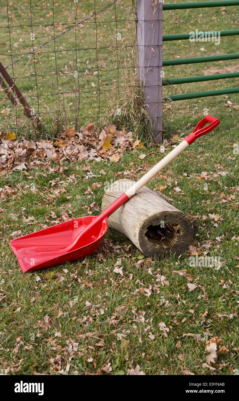 Red shovel and an old log being used as a lever and fulcrum - Stock Image