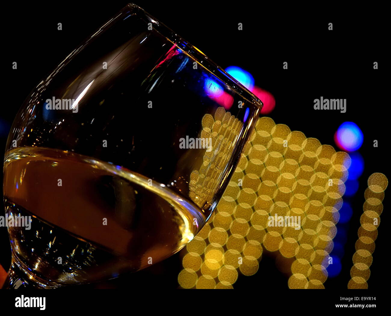 Half full wine glass with yellow bokeh behind it Stock Photo