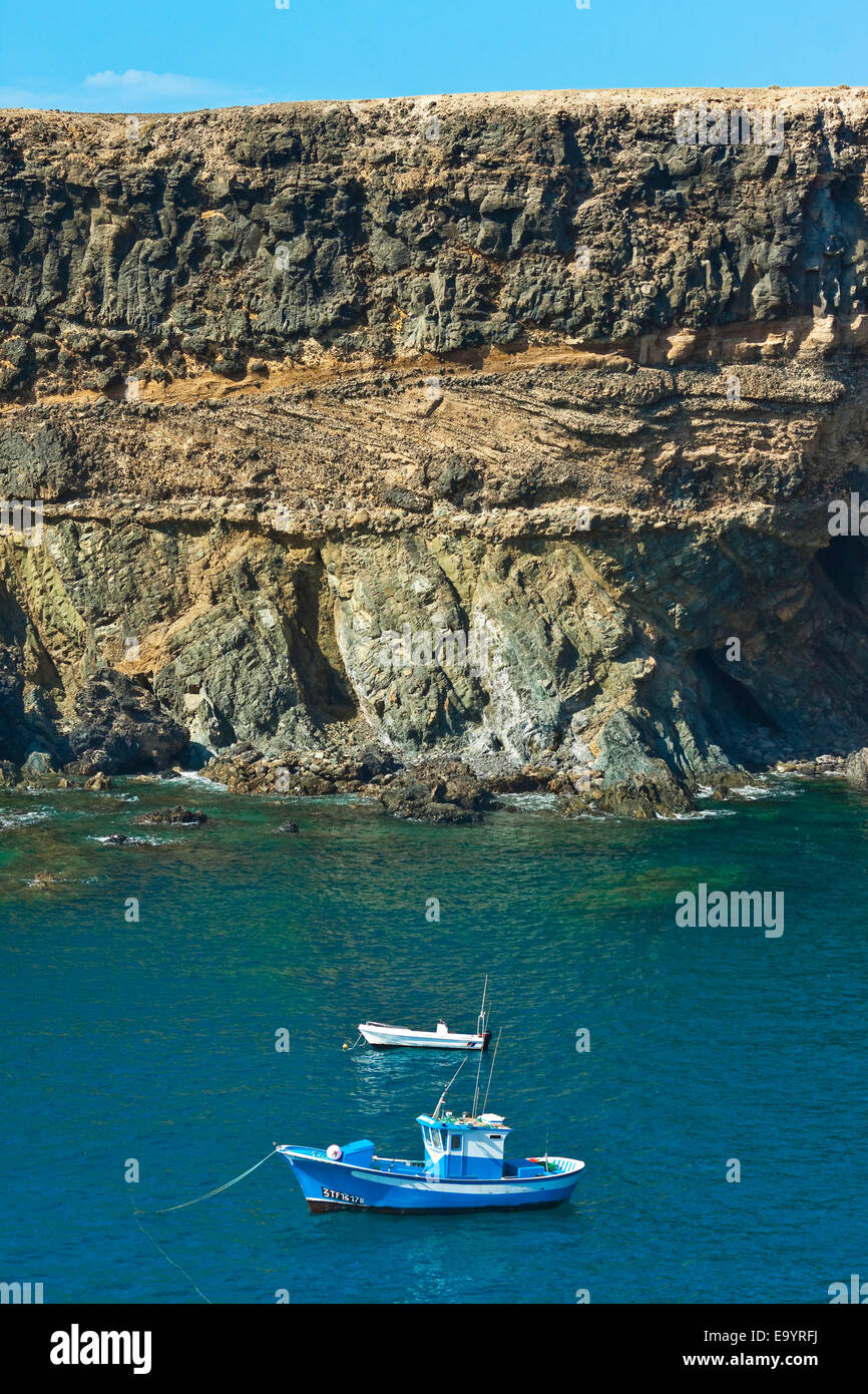 Boat moored at Caleta Negra (Black Bay) with pillow lava formed underwater in cliffs; Ajuy, Fuerteventura, Canary - Stock Image