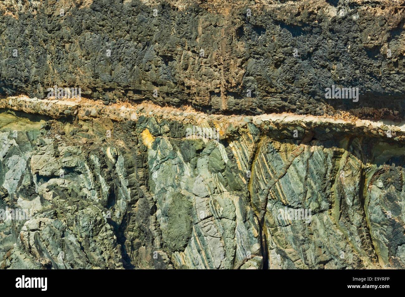 Unconformity of older Jurassic sediments & Pliocene limestone plus later lava on top at Caleta Negra; Ajuy, - Stock Image