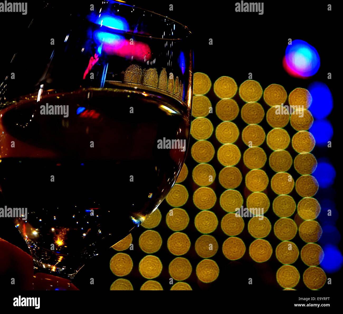Half full wine glass with yellow bokeh behind it Stock Photo