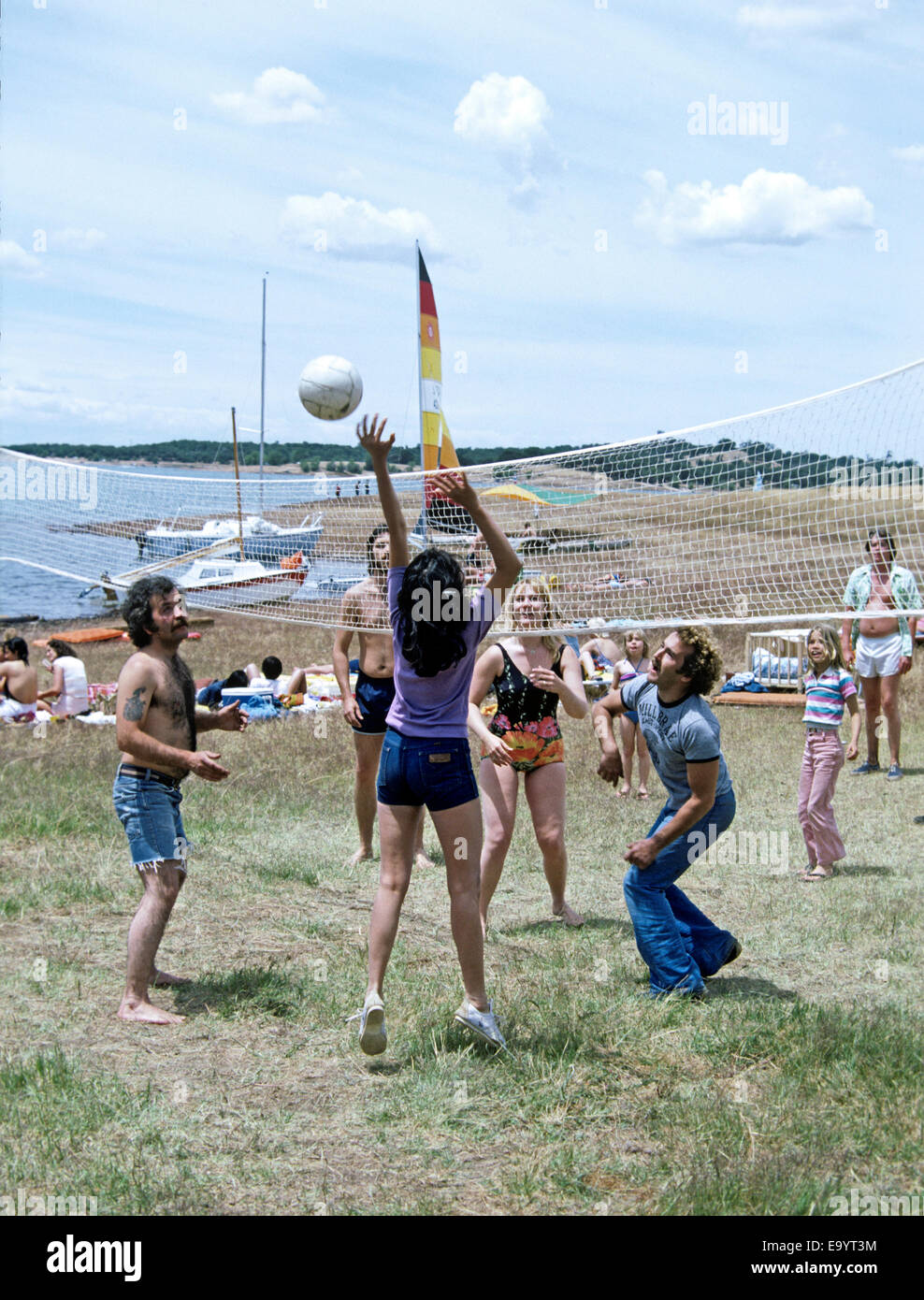 young adults play volleyball on holiday weekend in California - Stock Image