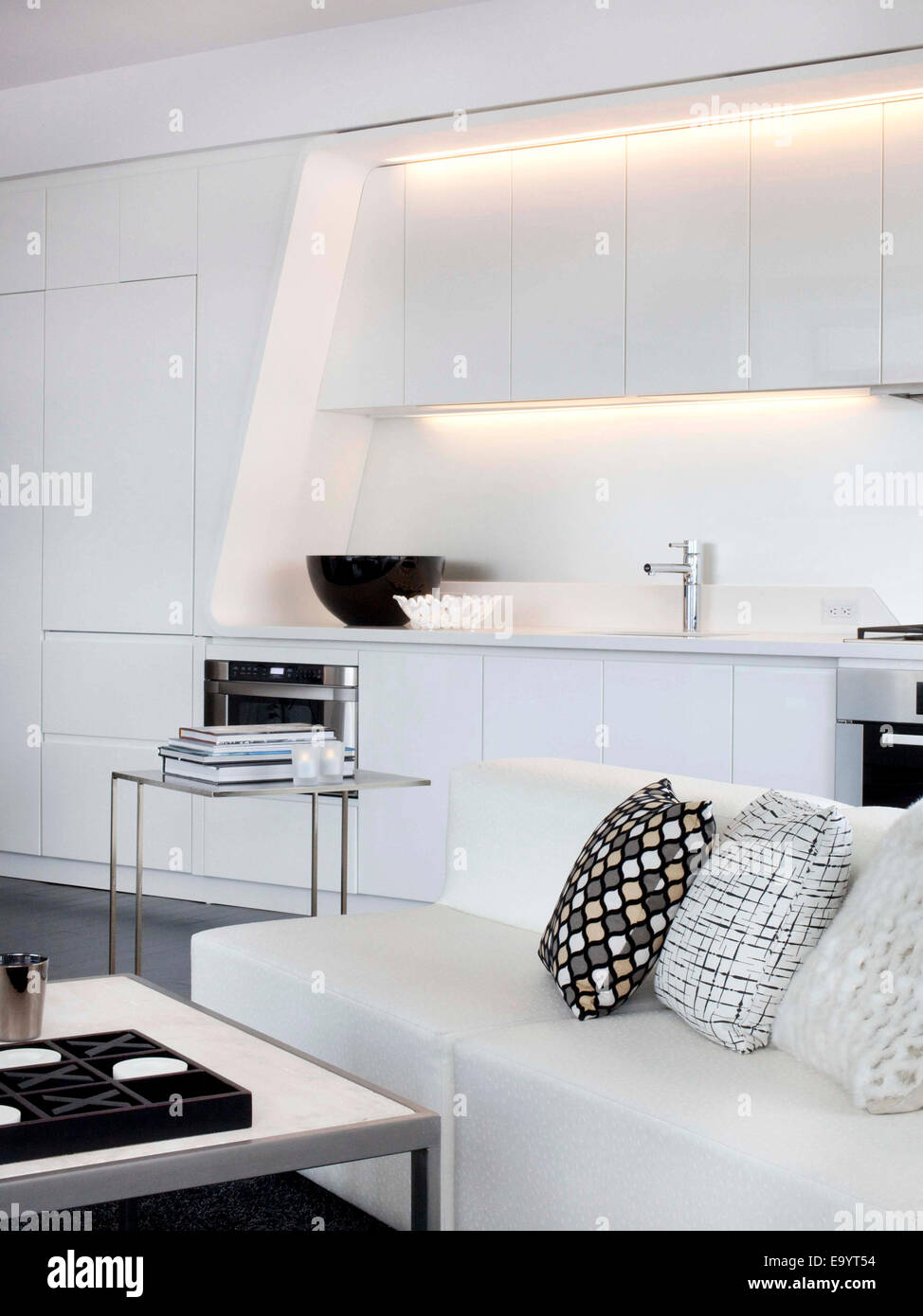 all white couch and kitchen in loft apartment - Stock Image