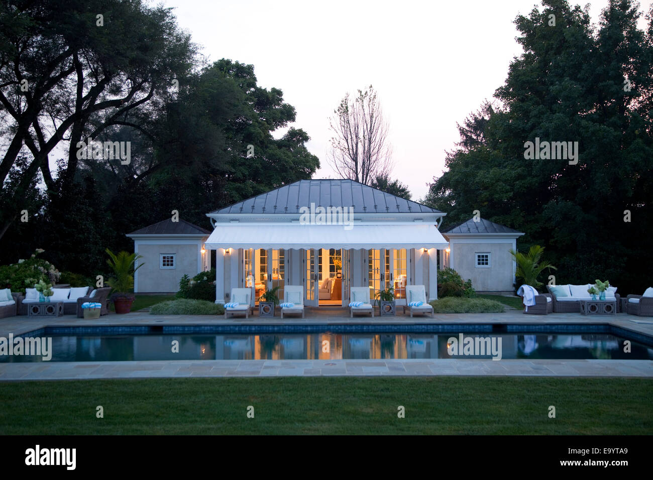 Swimming pool and pool house in early evening. - Stock Image