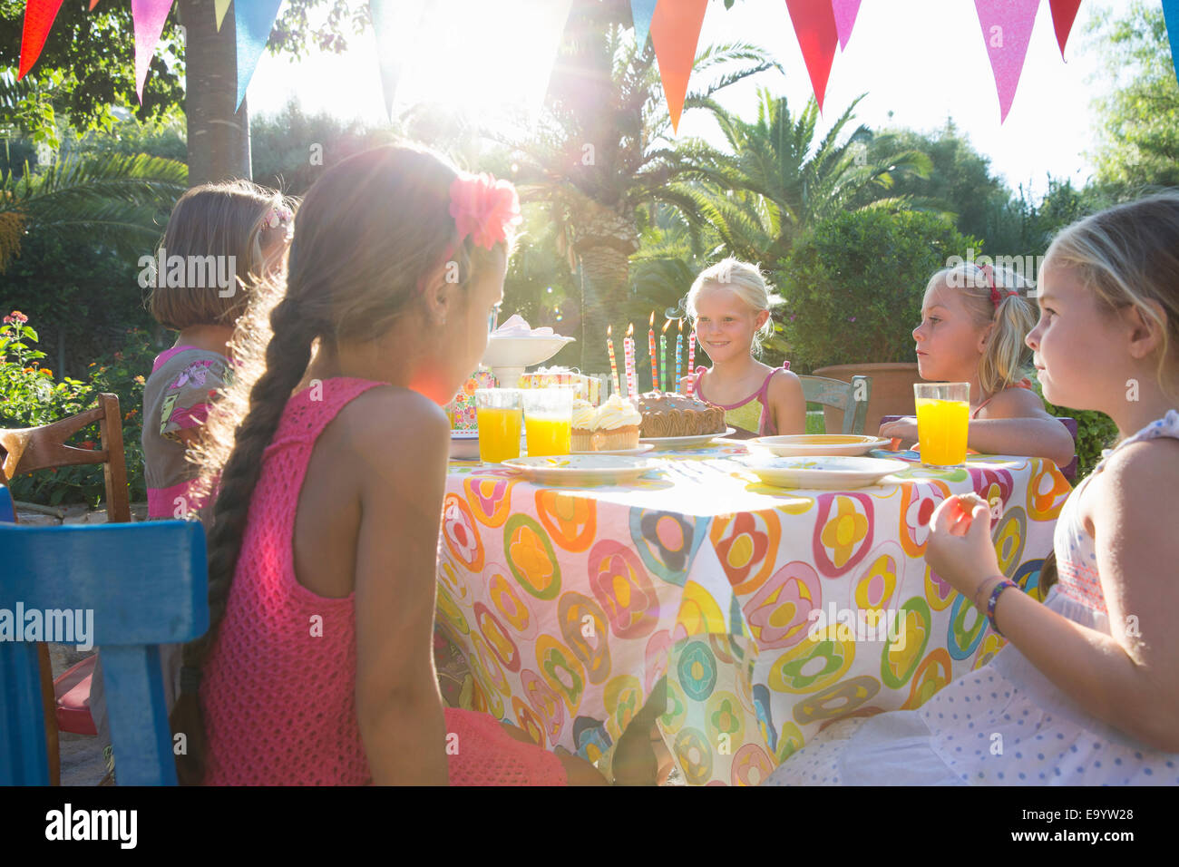 Girls sitting at table with birthday party food - Stock Image