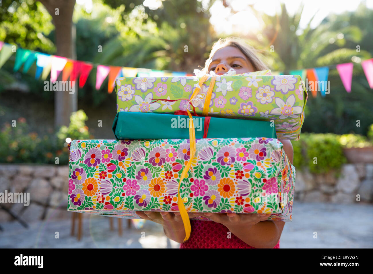 Girl carrying pile of birthday presents - Stock Image