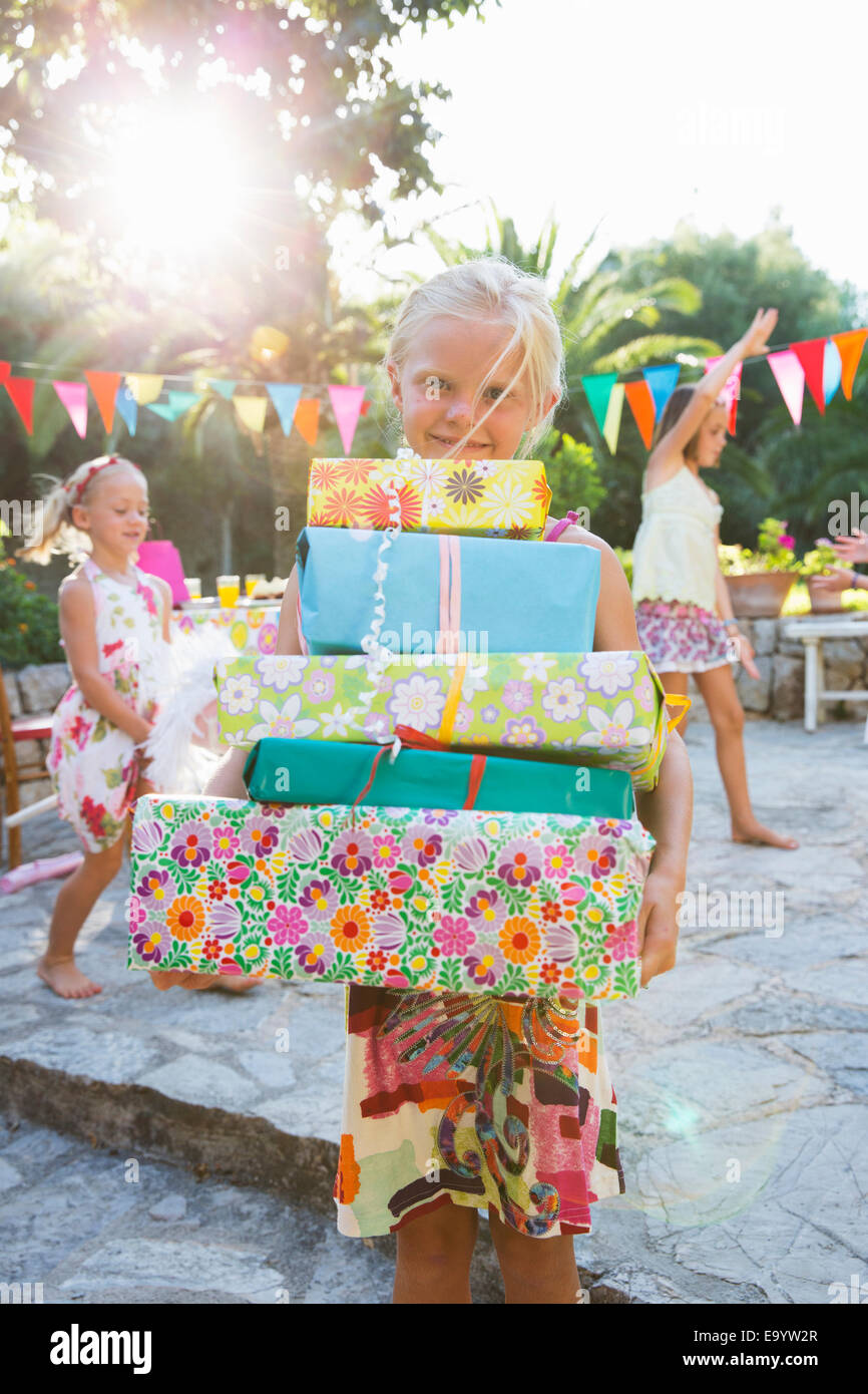 Girl with stack of birthday presents - Stock Image