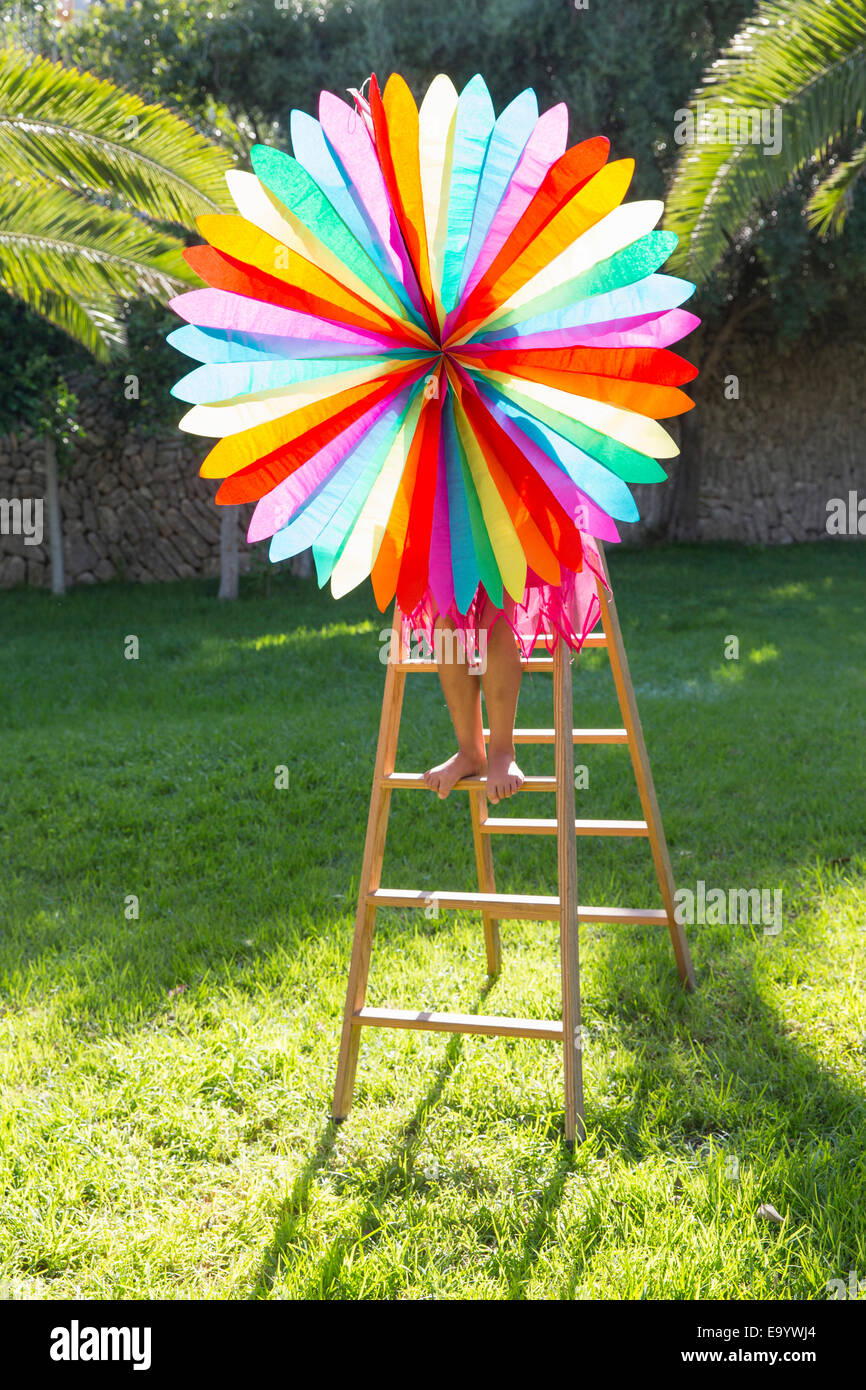 Girl putting up decoration in garden - Stock Image