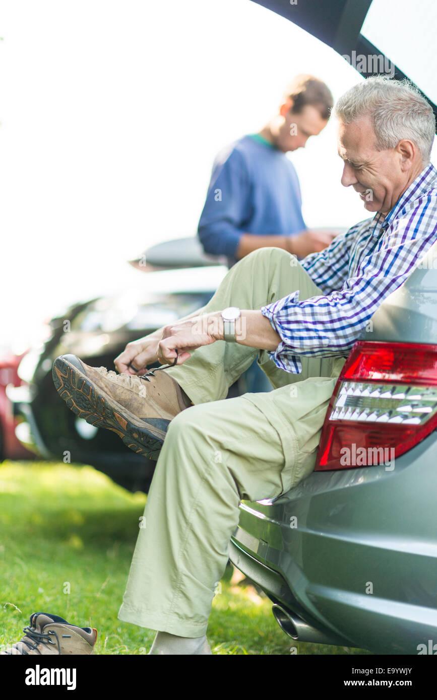 Man sitting on car boot tying shoelaces - Stock Image