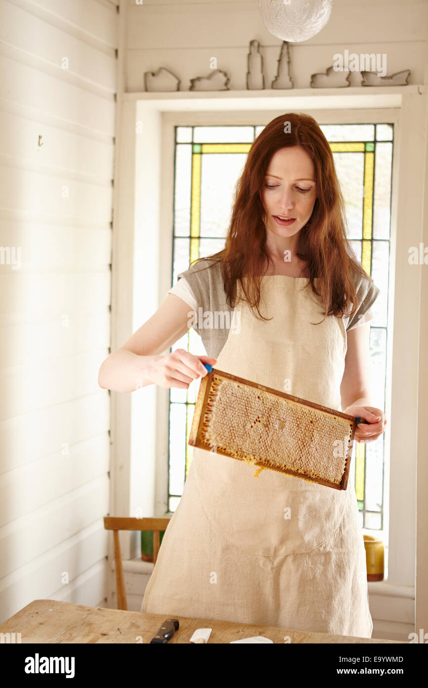 Female beekeeper in kitchen holding up 'super' from beehive (honeycomb tray) - Stock Image