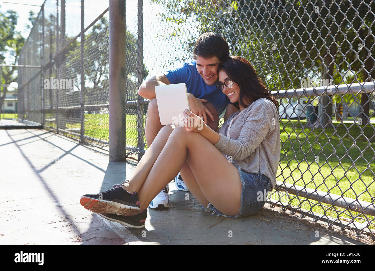 Young couple using digital tablet by wire fence - Stock Image