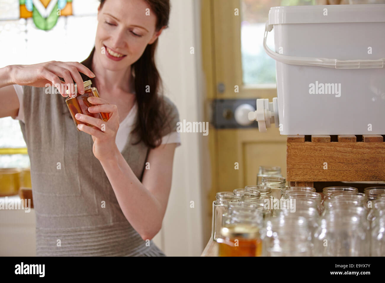 Female beekeeper in kitchen, bottling filtered honey from beehive - Stock Image