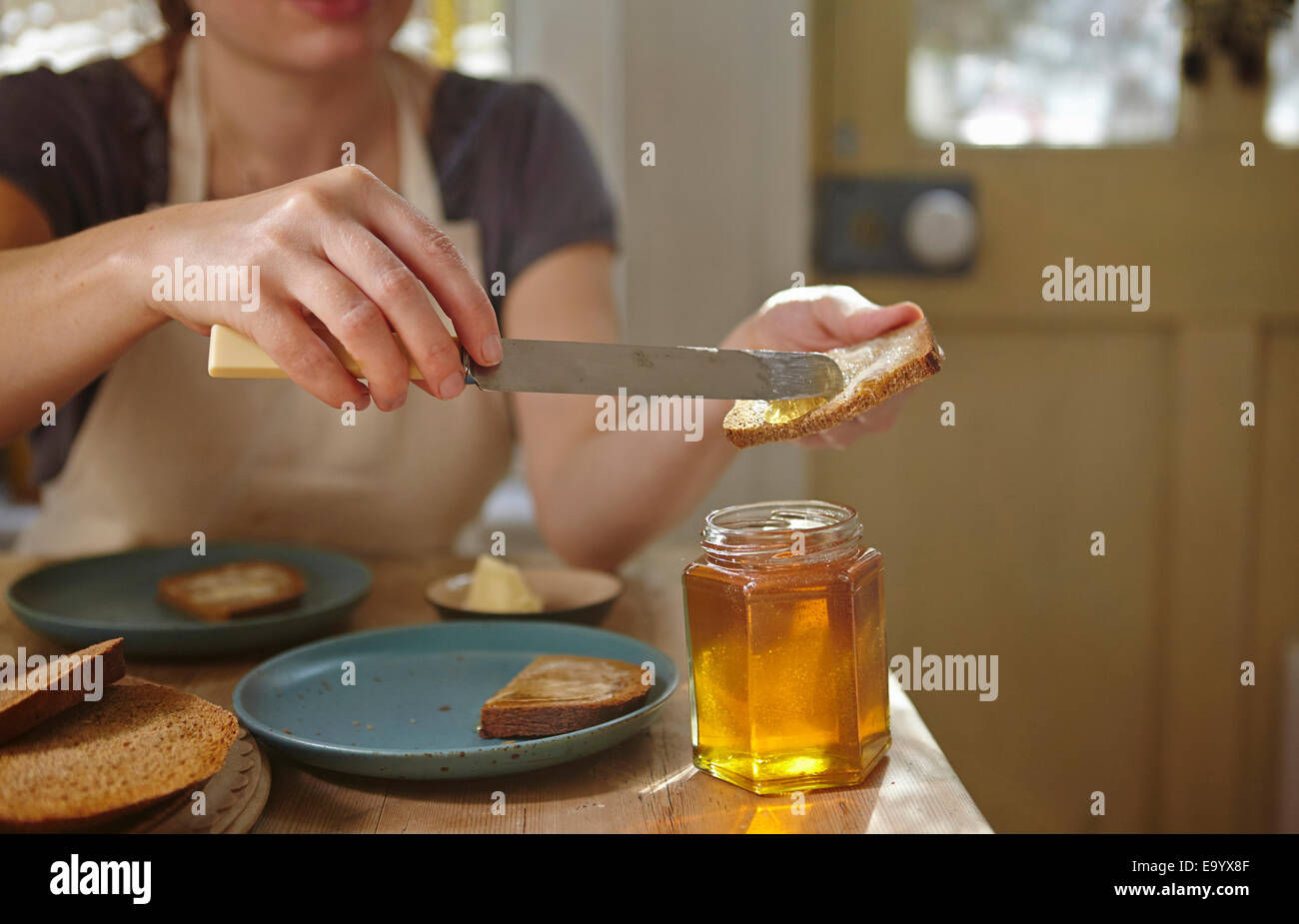 Woman tasting freshly extracted honey on bread - Stock Image