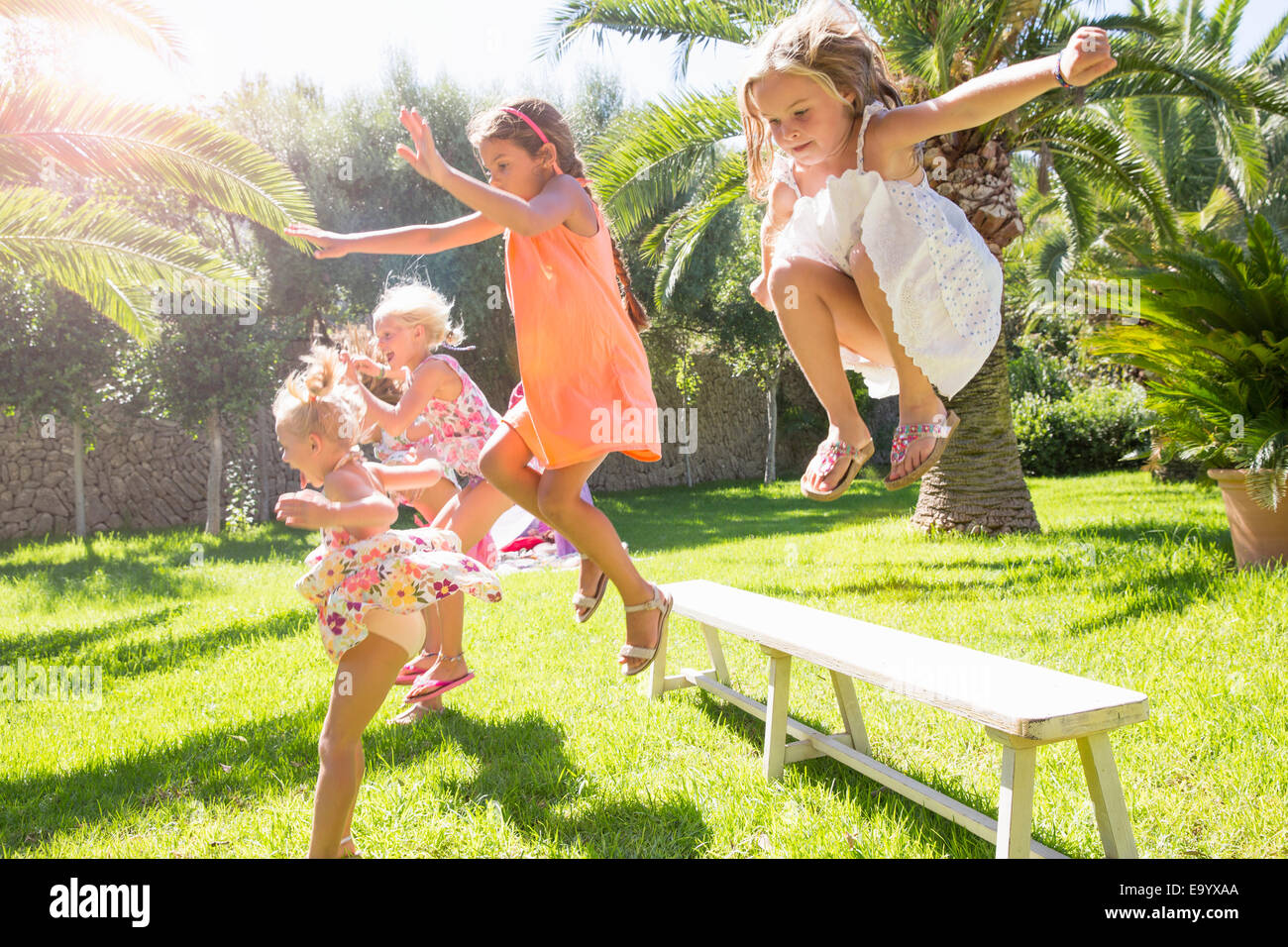 Five energetic girls jumping from garden bench Stock Photo