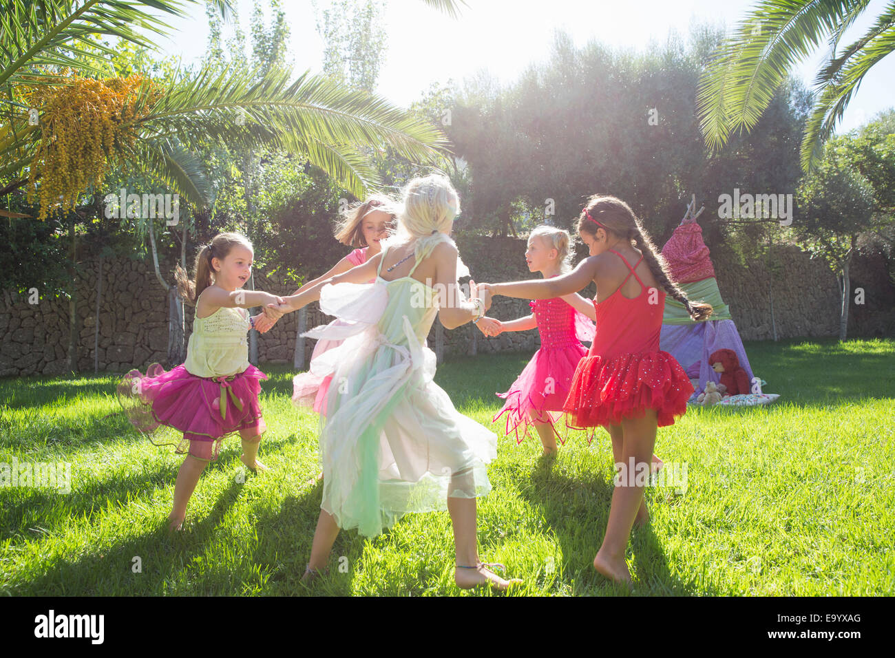 Five energetic girls in fairy costume playing in garden - Stock Image