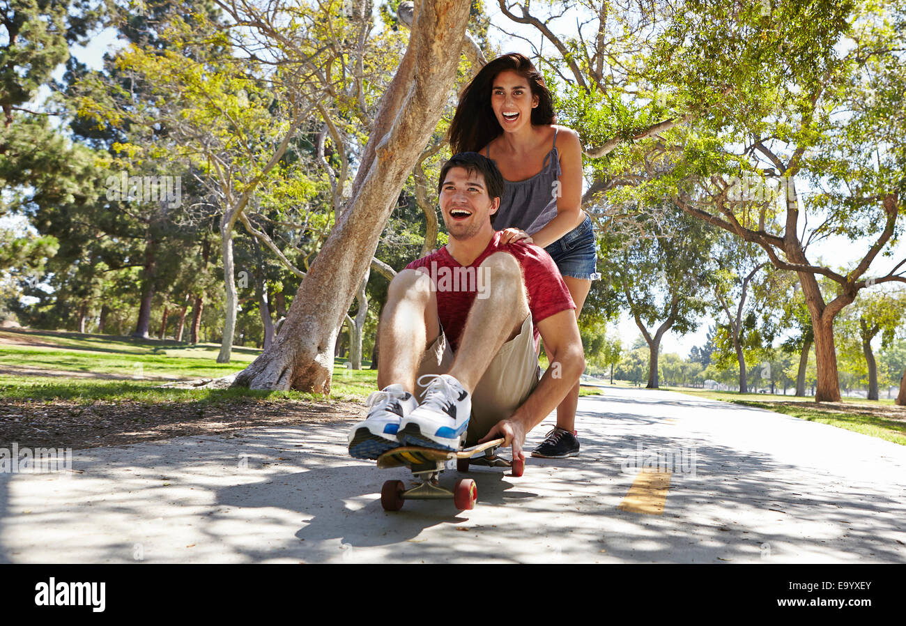 Young couple skateboarding in park - Stock Image