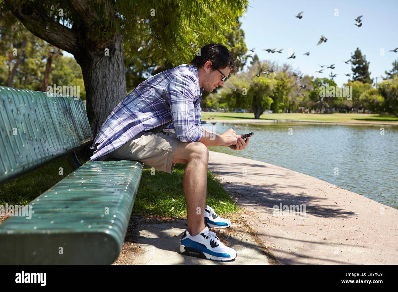 Man using phone on park bench Stock Photo
