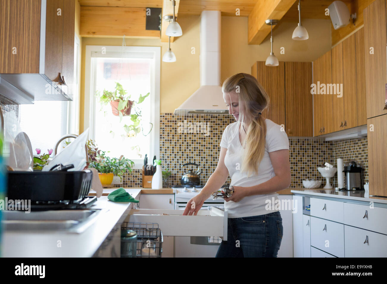 Young woman cleaning kitchen with green cleaning products - Stock Image