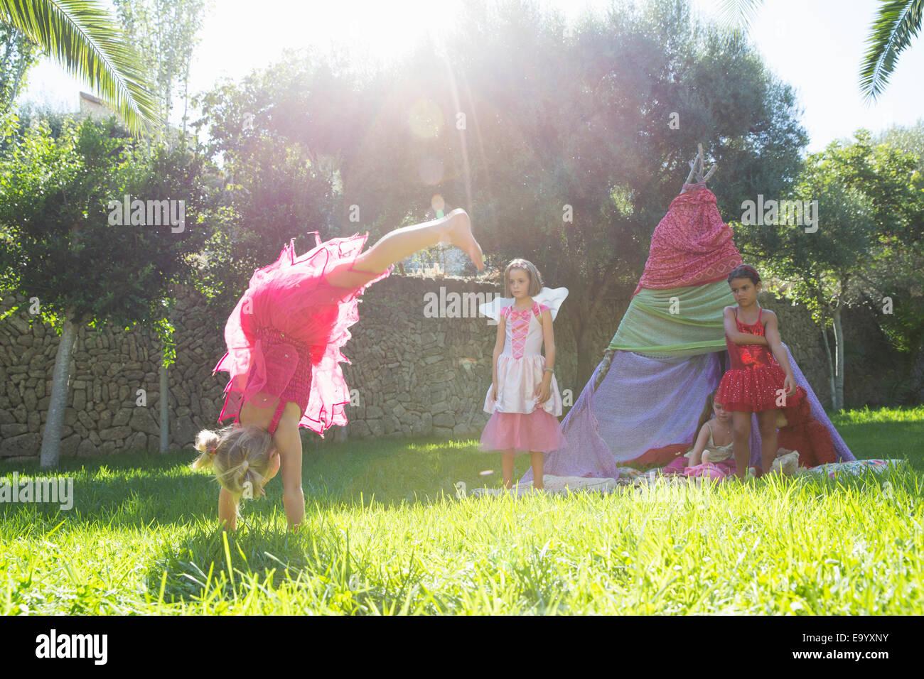 Girls watching friend in fairy costume doing handstand in garden - Stock Image