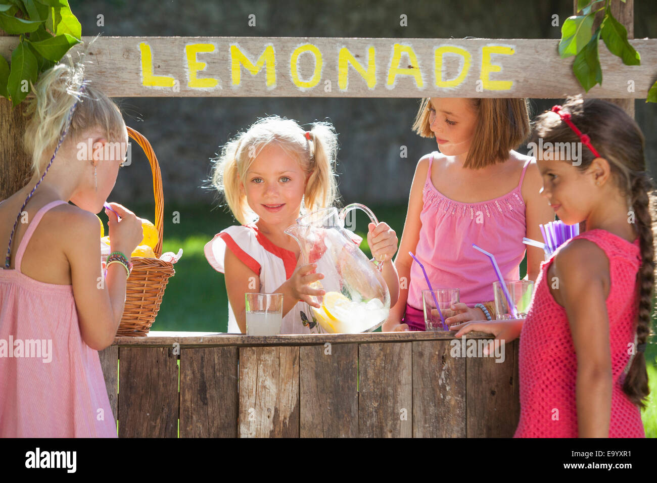 Candid portrait of four girls at lemonade stand in park - Stock Image