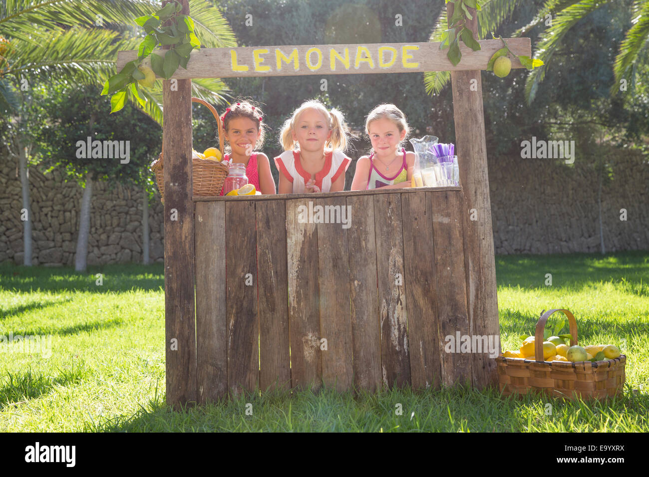 Portrait of three girls selling lemonade at stand in park - Stock Image