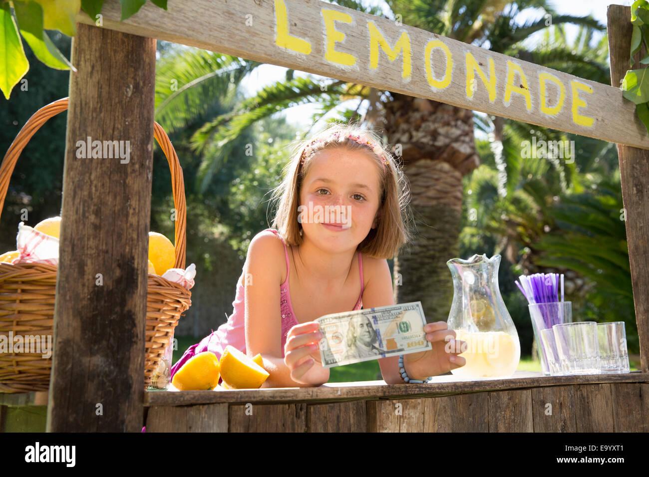 Portrait of girl on lemonade stand holding up one hundred dollar bill - Stock Image