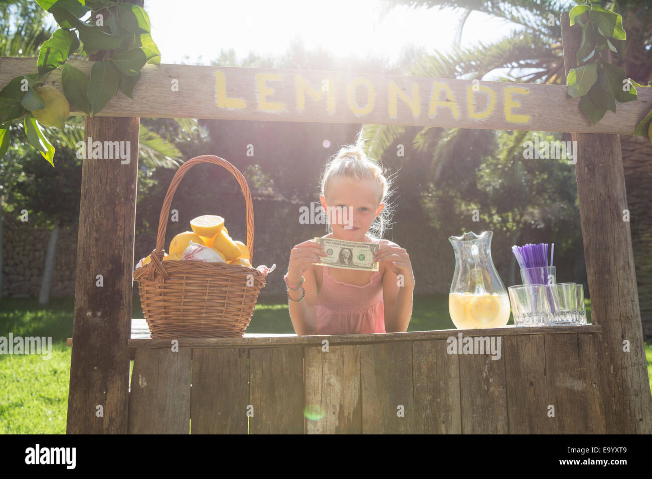 Portrait of girl on lemonade stand holding up one dollar bill - Stock Image