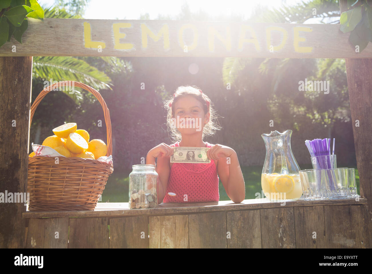 Portrait of proud girl on lemonade stand holding up one dollar bill - Stock Image