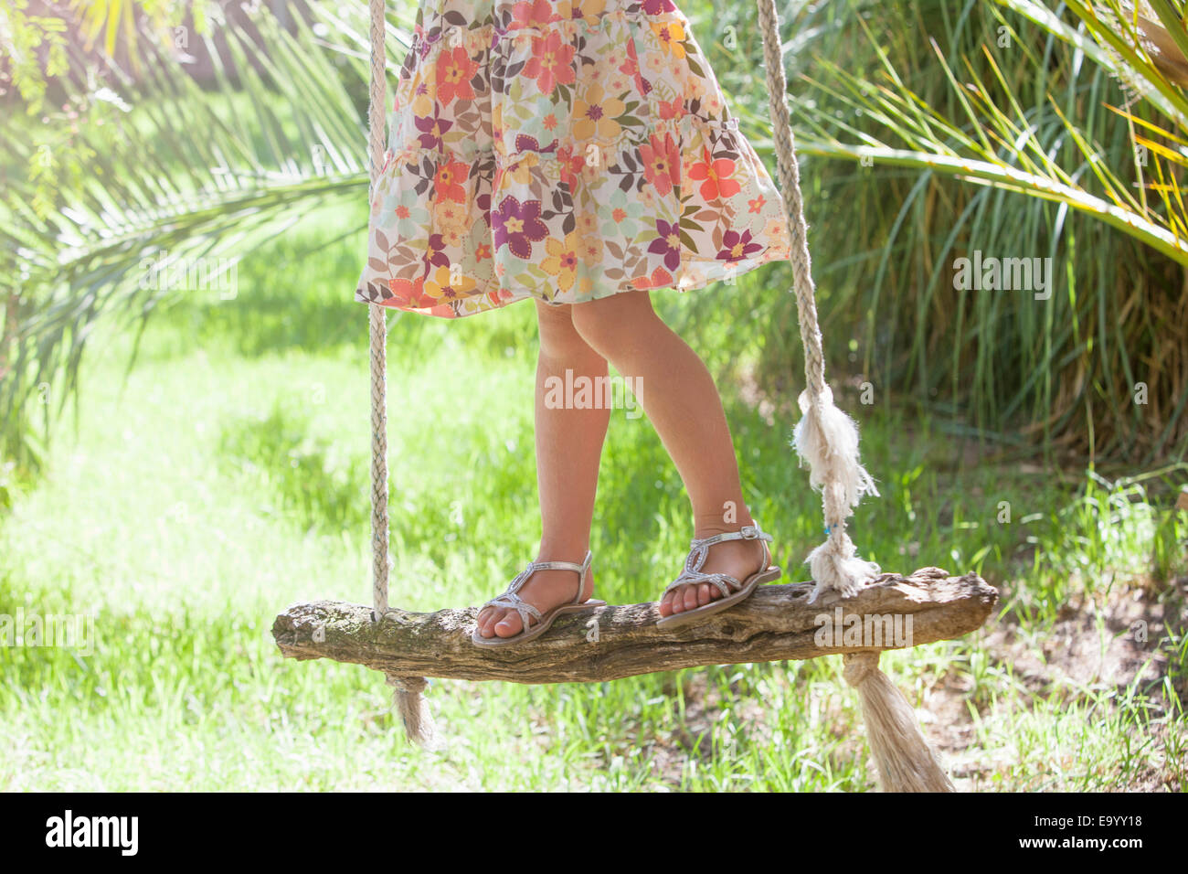 Waist down cropped shot of girl standing on tree swing in garden - Stock Image