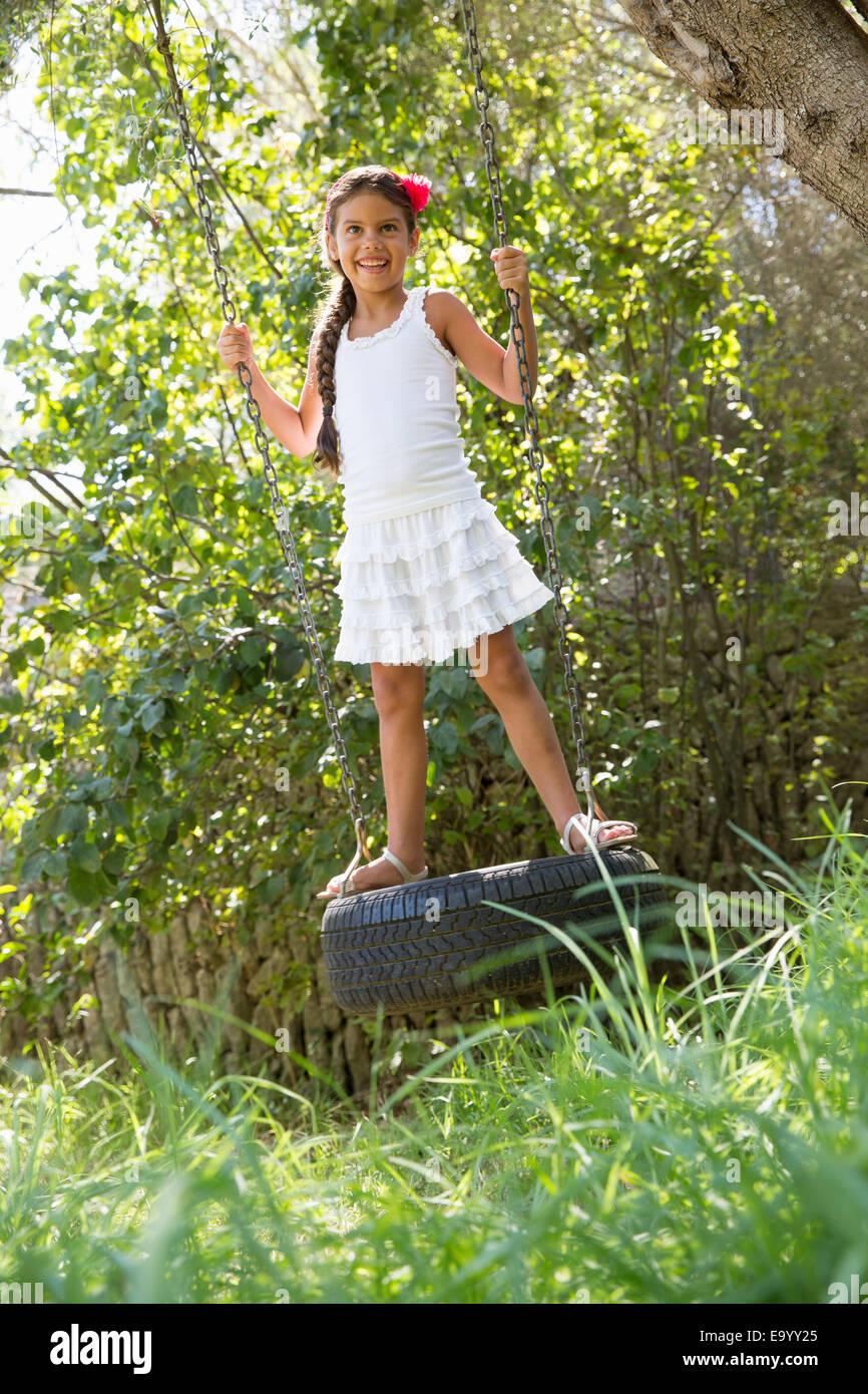 Girl standing swinging on tree tire swing in garden - Stock Image