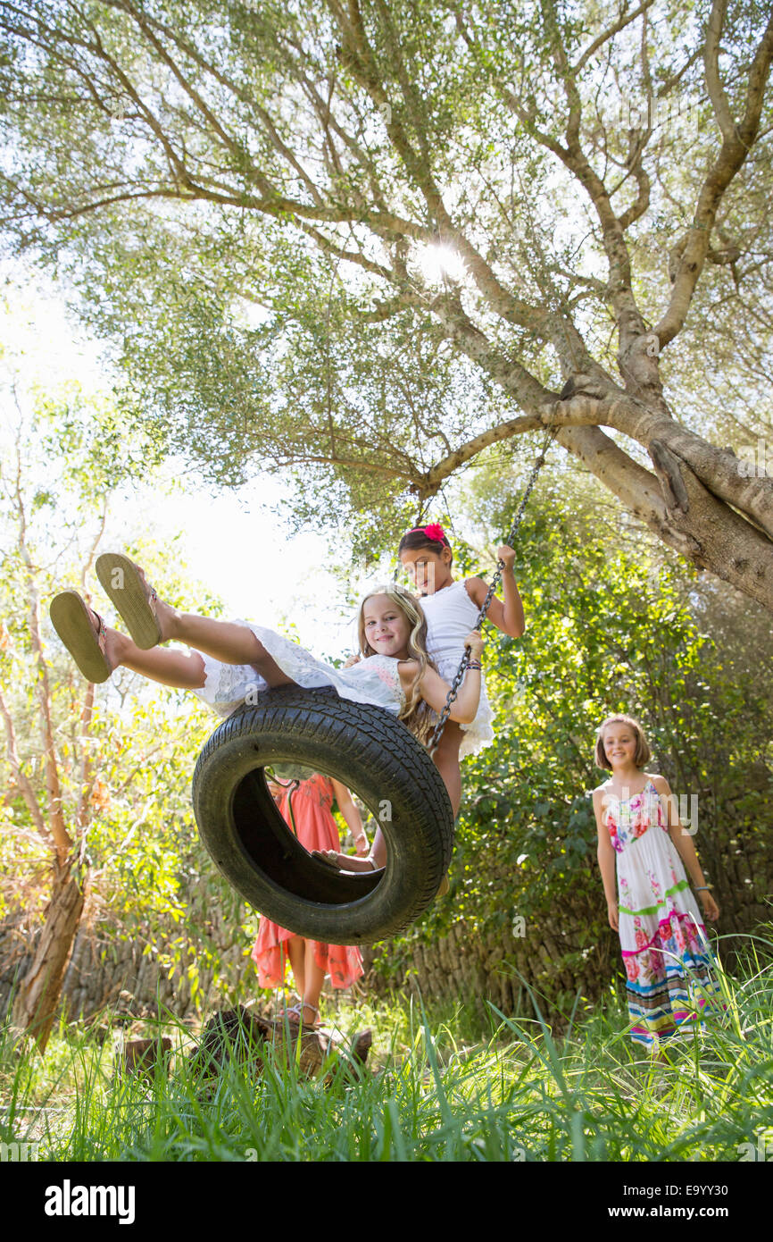 Low angle view of four girls playing on tree tire swing in garden - Stock Image