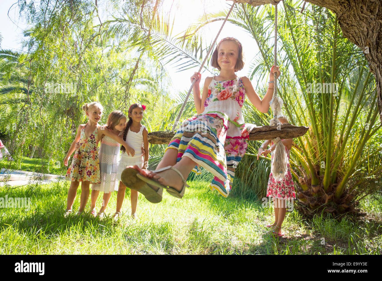 Girls queueing for tree swing in garden Stock Photo