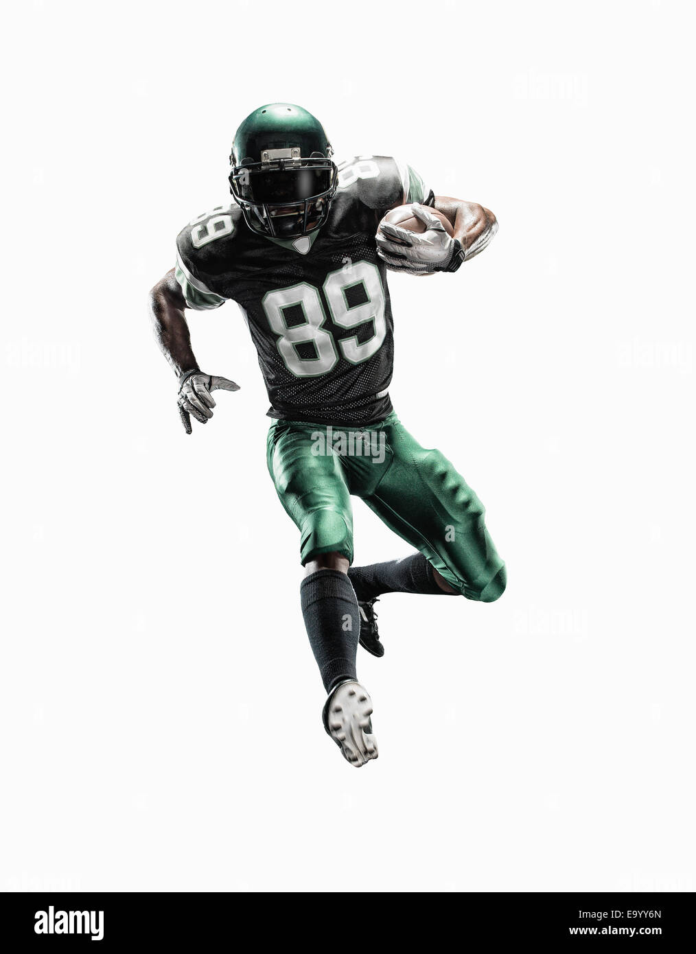 Studio shot of young male football player running with ball Stock Photo