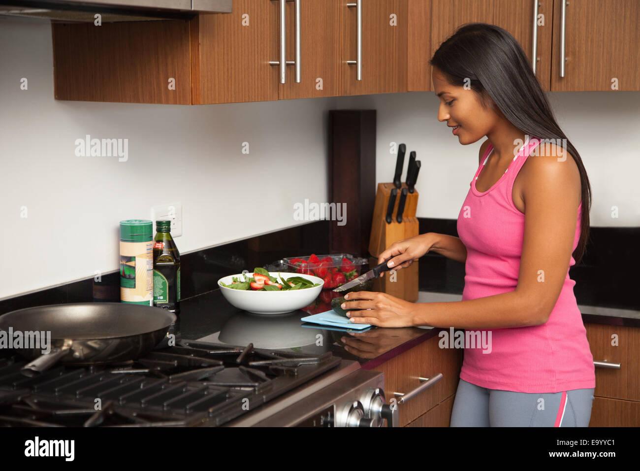Woman preparing salad in kitchen - Stock Image