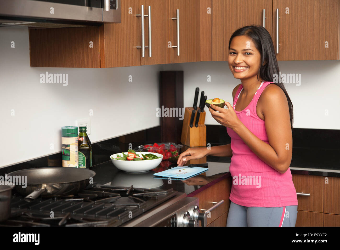 Woman preparing salad in kitchen - Stock Image
