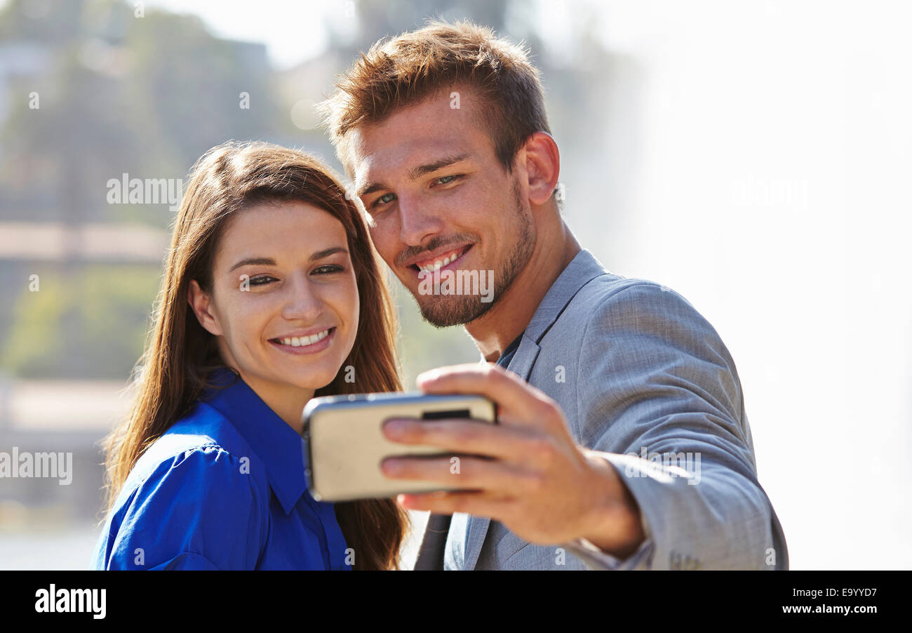 Businessman and woman taking selfie - Stock Image