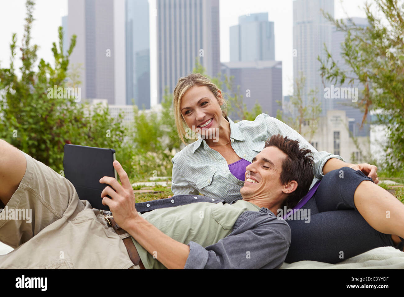 Couple relaxing in park by city Stock Photo