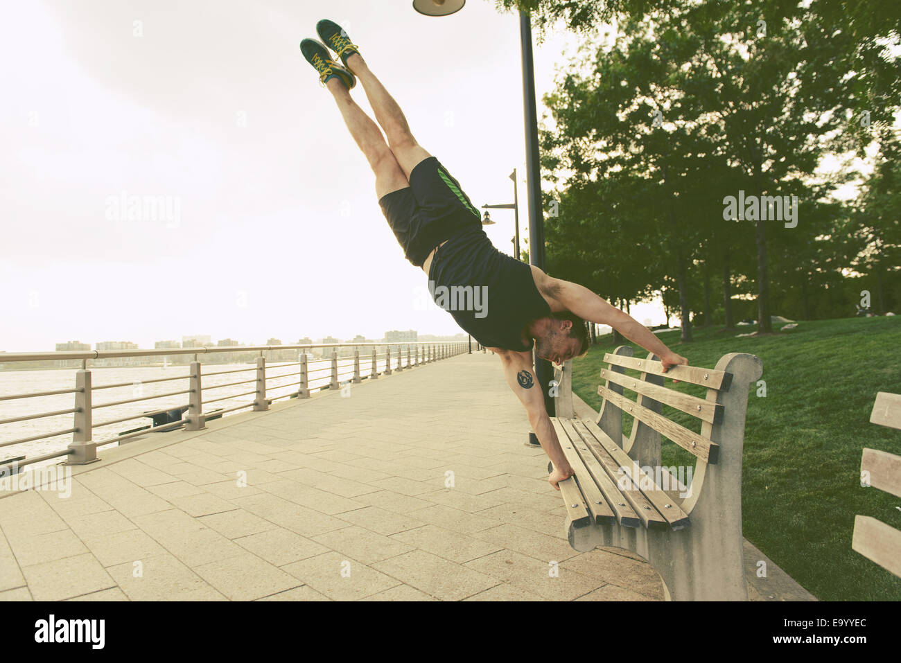 Young man doing handstand on riverside park bench - Stock Image