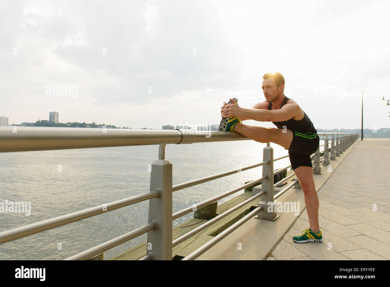 Young man touching toes on riverside railings - Stock Image