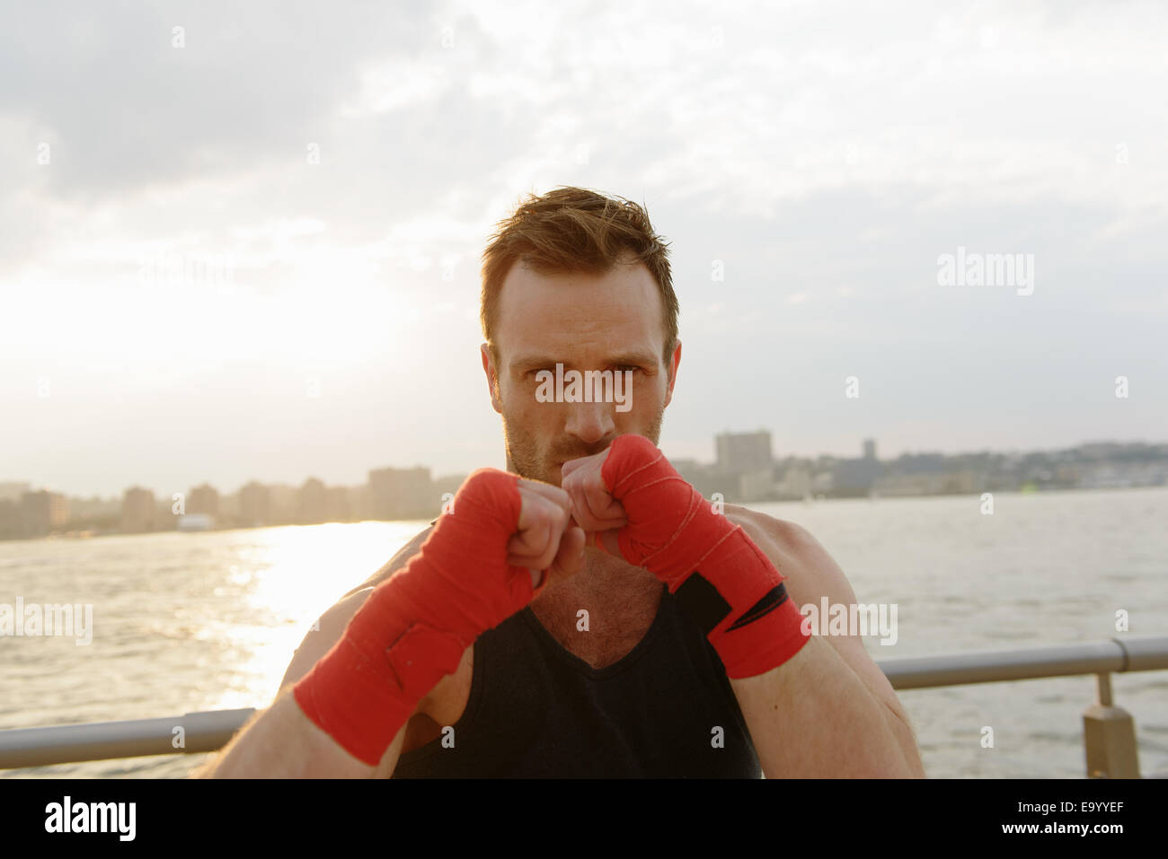 Portrait of young male boxer exercising on riverside - Stock Image