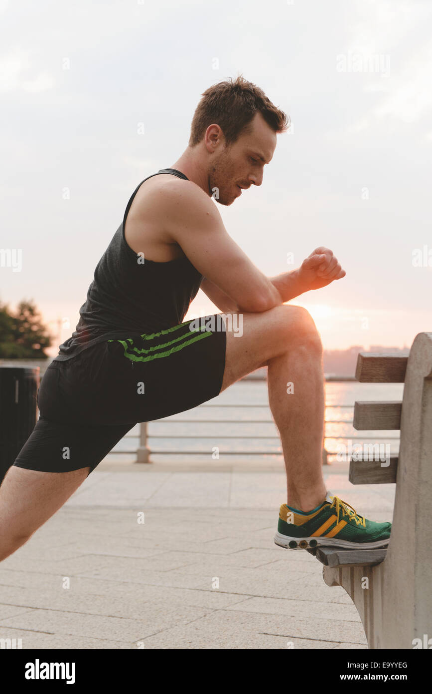 Young man doing warm up exercises on riverside bench - Stock Image