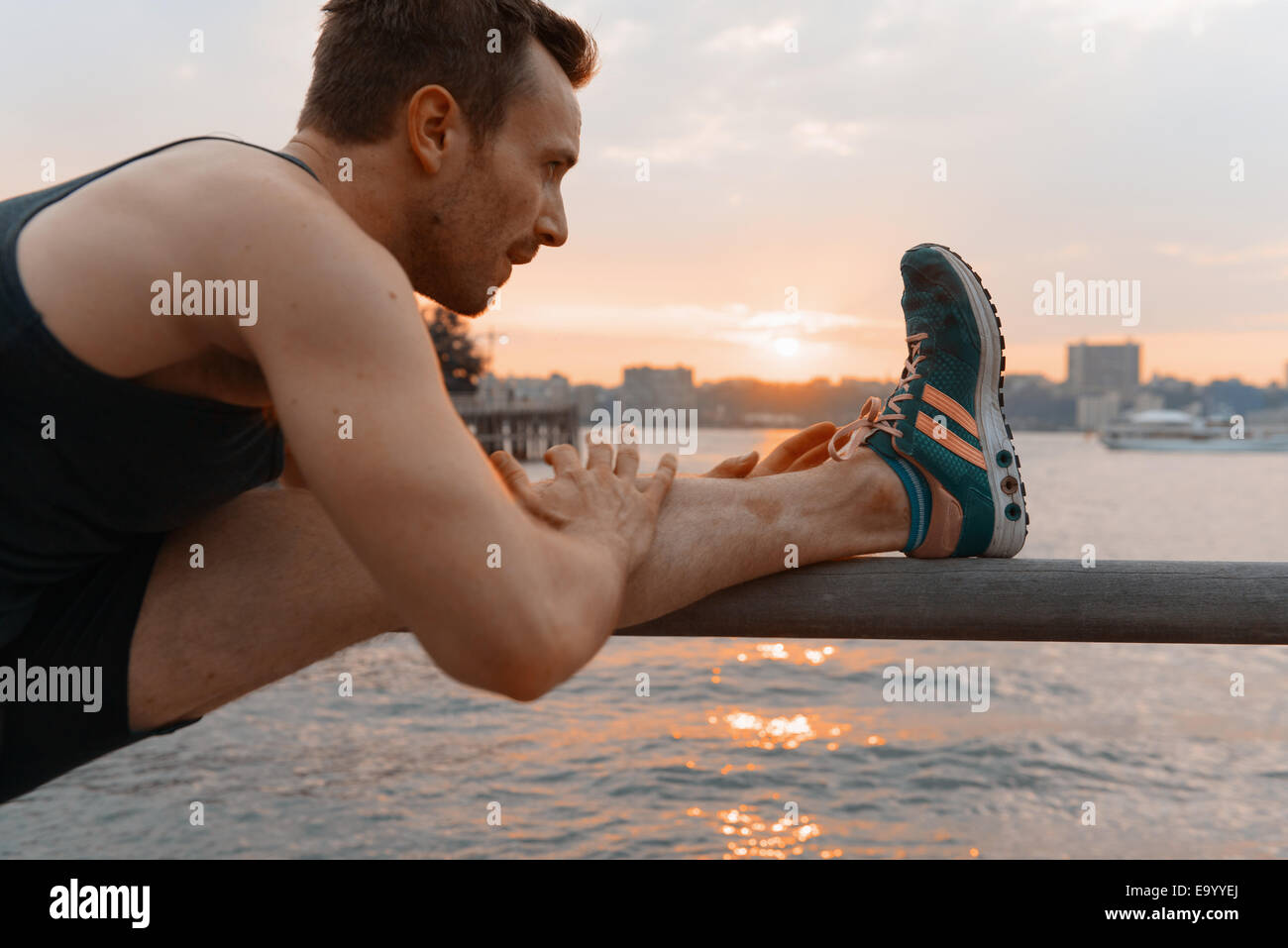 Young man touching toes on riverside railings at sunrise - Stock Image