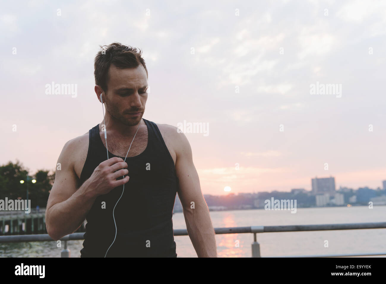 Young male runner listening to earphones on riverside at sunrise - Stock Image