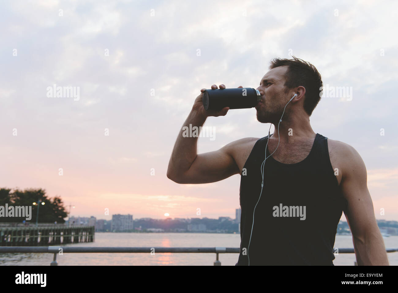 Young male runner drinking water on riverside at sunrise - Stock Image