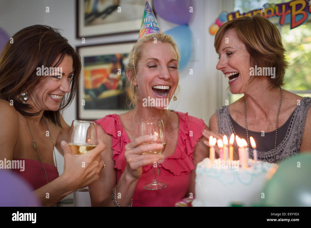 Three mature women at birthday party, laughing - Stock Image