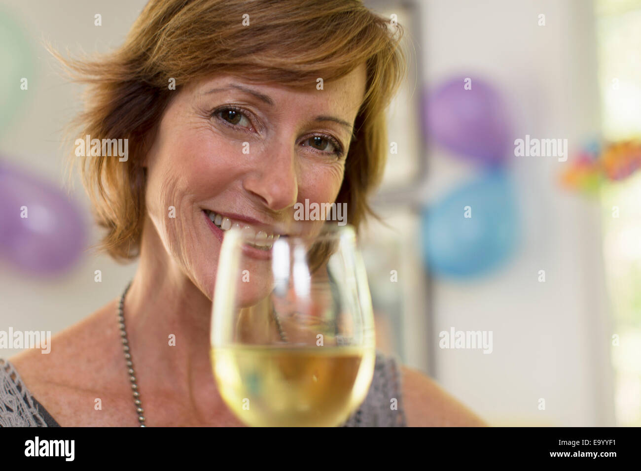Portrait of mature woman holding glass of wine - Stock Image