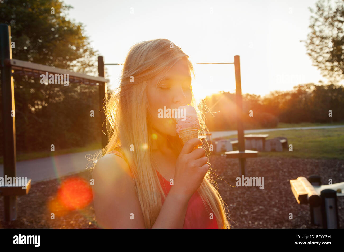 Young woman eating ice cream cone in park at sunset - Stock Image
