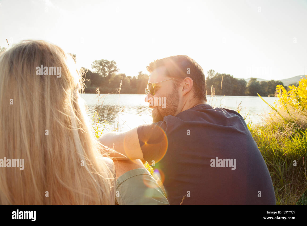 Young couple sitting on riverbank Stock Photo